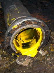 Crude palm oil seeping from a loading pipe © Greenpeace/Woolley